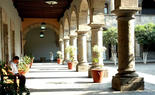 Visitors under the colonade, potted plants, arch, walkway, lamps, trees, stone, graceful proportions in architecture, Governor's Palace, Guadalajara, Jalisco, Mexico by Wonderlane