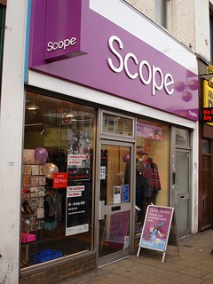 The same shop with a new sign in white letters on a reddish-purple background.