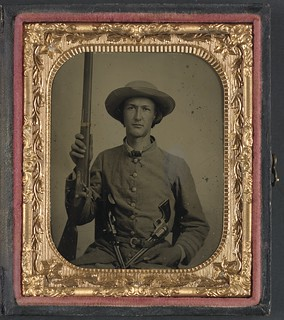 [Unidentified soldier in Confederate infantry uniform with model 1842 musket and two Colt revolvers] (LOC)