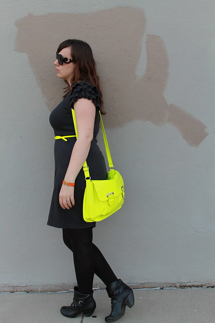 Neon and charcoal outfit: black booties, black tights, knit charcoal dress with ruffled shoulders, neon belt, neon satchel, Prada baroque sunglasses, rose gold watch, two-tone diamond watch