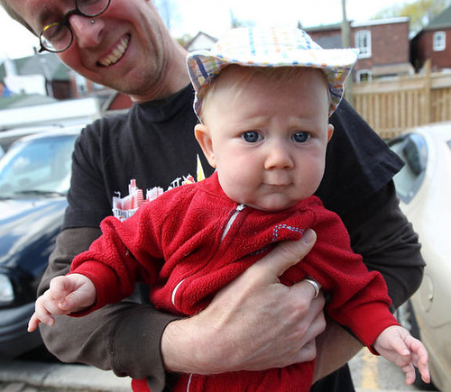 "The so-called ""genderless baby"" named Storm, being held by a parent. The baby wears a hat and a red hoodie and makes a funny expression with furrowed brows."