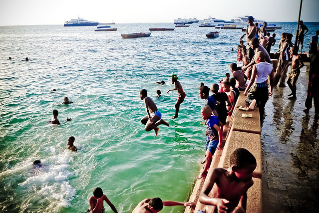 Kids jump off the promenade in Stone Town, Zanzibar