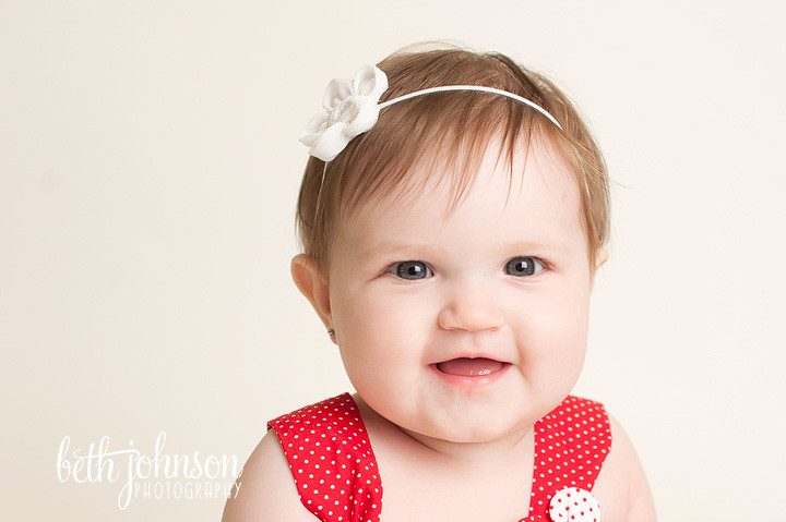 beautiful baby girl in studio on white backdrop red and white polka dots