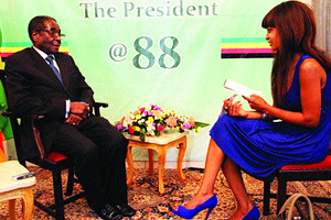 Republic of Zimbabwe President Robert Mugabe with Deputy Editor of the Sunday Mail Nomsa Nkala on the eve of his 88th birthday. Zimbabwe has fought western sanctions for over two decades. by Pan-African News Wire File Photos