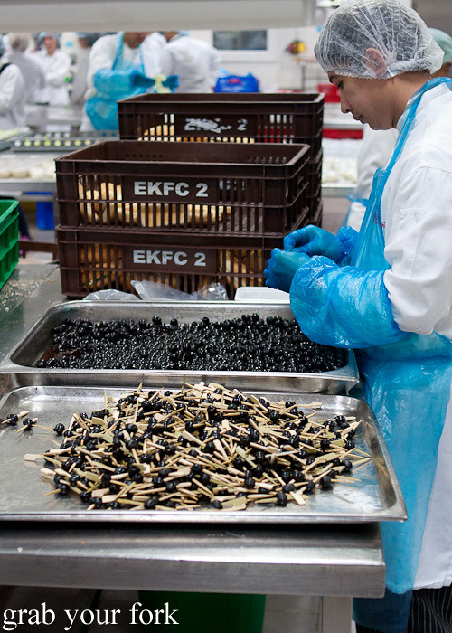 Threading olives onto toothpicks during a behind-the-scenes tour of Emirates Flight Catering