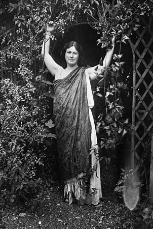 A photo of Isadora Duncan in her famous flowing grecian tunic standing in a garden surrounded by trees and plants.