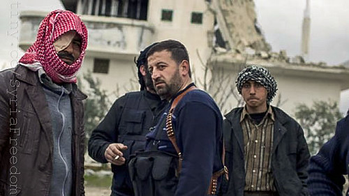 Free Syrian Army soldiers gather outside a house destroyed in fighting against President Assad's forces in Sarmin, north of Syria, Tuesday, Feb. 28, 2012.