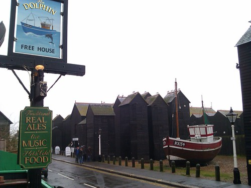 A boat, net huts and a pub sign