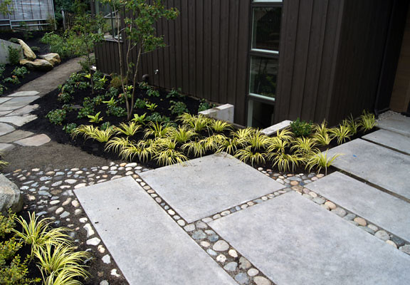 Grasses and river rock punctuate simple rectangular tiles.