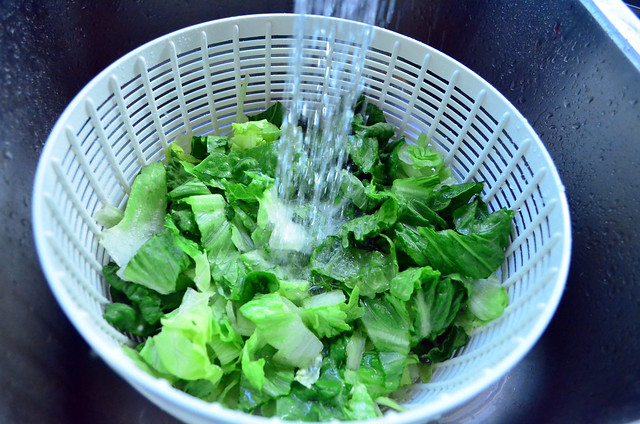 A colander with chopped lettuce being rinsed in the sink.