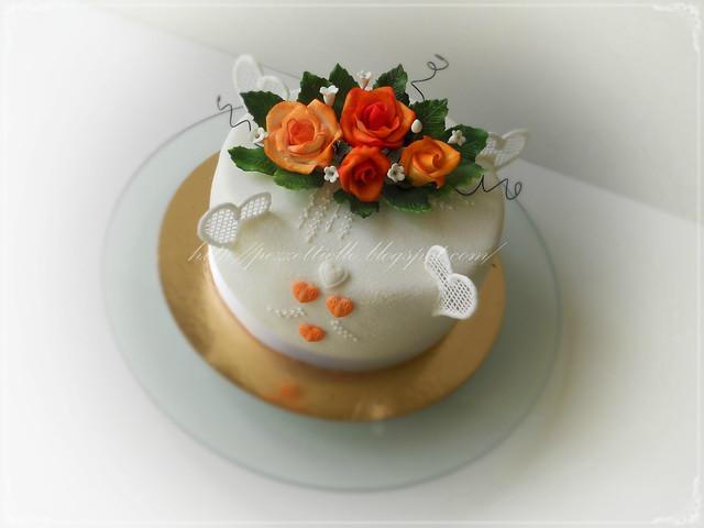 Torta con rose arancio e cuori, pizzo coperta in pasta di zucchero setosa, decori in ghiaccia real