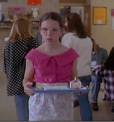 Bespectacled girl wearing a bright pink blouse and holding a lunch tray of food.