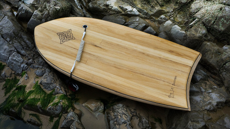Fibreglassed foam core, with tulipwood deck and balsa rails and base. Twin finned modern paipo