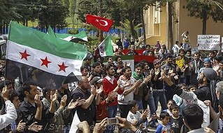Syrian refugees wave Turkish and Syrian Independence flags during a protest against Syria's President Bashar al-Assad at Yayladagi refugee camp in Hatay province near the Turkish-Syrian border in April 2012.(via Creative Commons, FreedomHouse2)