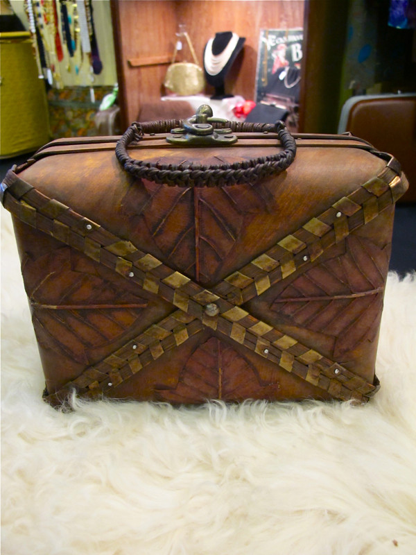 Rustic leaf-motif box bag with bronze strips and a woven handle