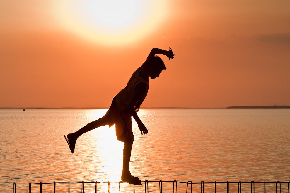 """Un travieso niño camina sobre lo que sería la estructura de metal de un muro de contención sin terminar, en la playa """"San José"""" de la costanera de Encarnación en la víspera de la semana santa, en horas de la tarde. (Elton Núñez)."""