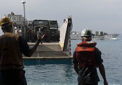 WHITE BEACH NAVAL FACILITY, Okinawa (March 3, 2012) Landing Craft Utility (LCU) 1631 is guided to the forward-deployed amphibious dock landing ship USS Tortuga (LSD 46) by Boatswain's Mate 3rd Class Jonathan Miller as Boatswain's Mate 3rd Class Christian Riddle stands ready to cast a heaving line to begin stern gate marriage operations to unload U.S. Marine 7-ton trucks as LCU 1627 passes behind. (U.S. Navy photo by Mass Communication Specialist 2nd Class Eric Crosby)