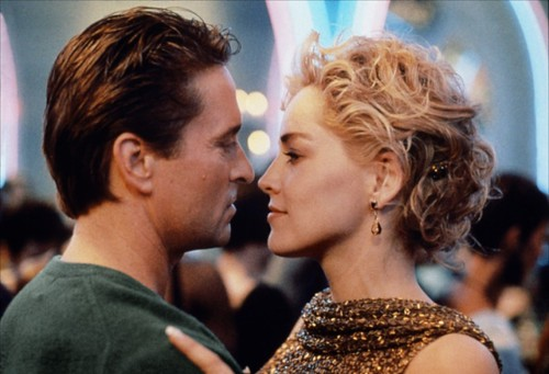 "This is a still from ""Basic Instinct."" A man and a woman face each other, with their faces close together, as if to kiss. The man is wearing gray, and the woman is wearing shimmery gold. They appear to be in a crowded, well-lit room."