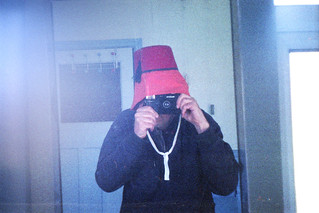 reflected self-portrait with Keystone Everflash 3570 camera, sou' wester and Fez