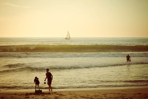 Kids, bodysurfer and sailboat
