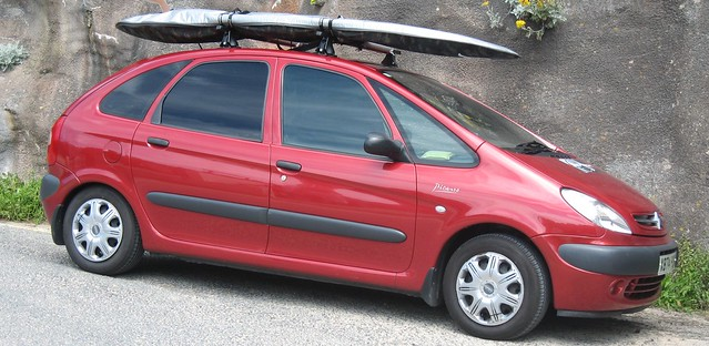 COol, red Citroen Xsara Picasso with surfboard on the roof, at beach, Newquay, Cornwall
