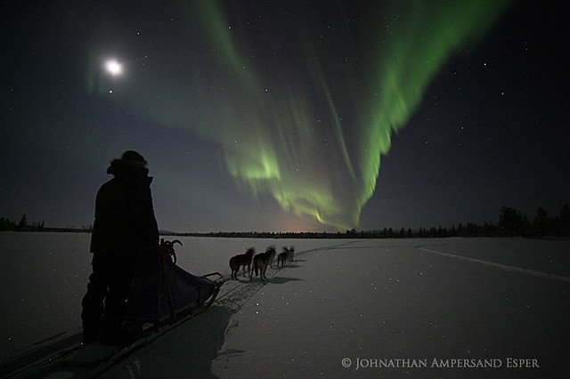 dogsled musher under a full moon, near Kiruna, Sweden