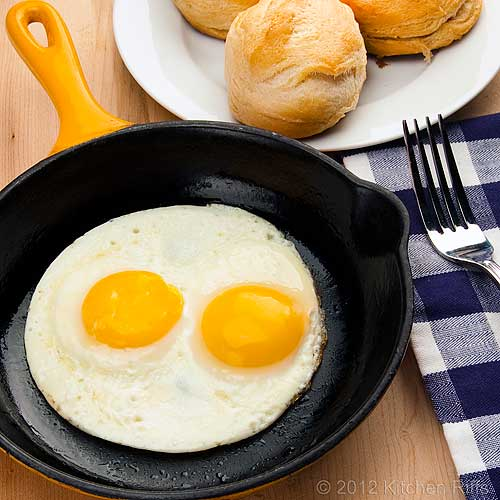 Fried Eggs in Pan with Plate of Biscuits