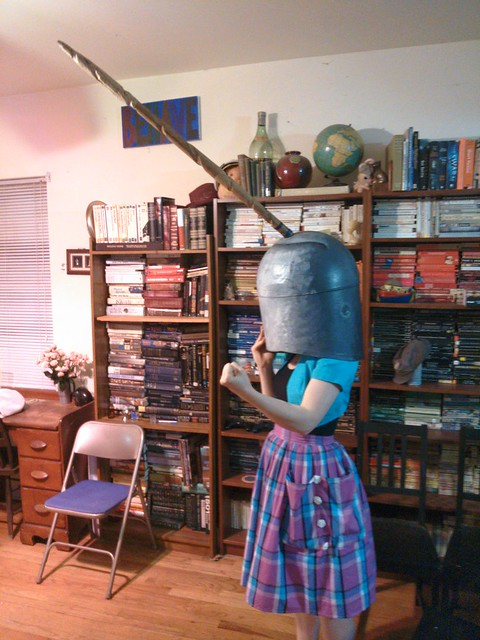A woman in a turquoise bolera and plaid skirt does a Rosie the Riveter pose while wearing a narwal head mask