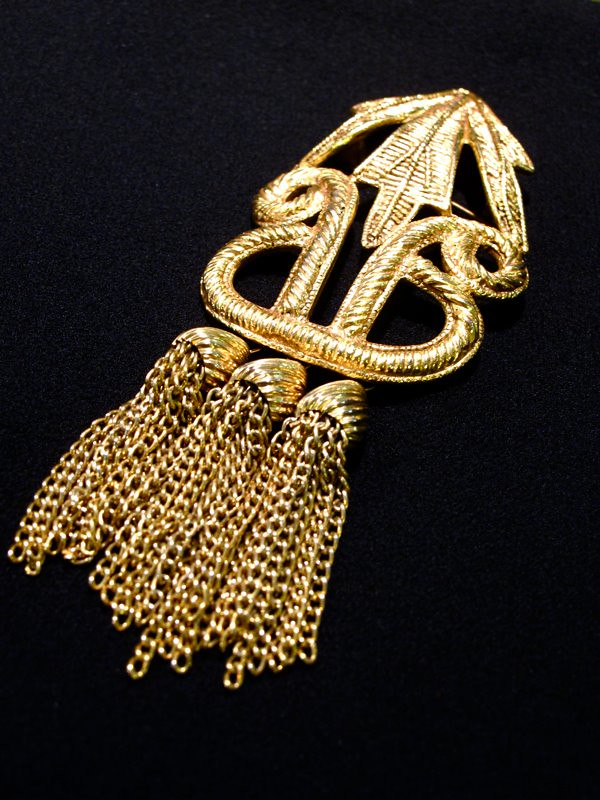 Shake it up with this  Dauplaise-signed gold-tone brooch with tassels!