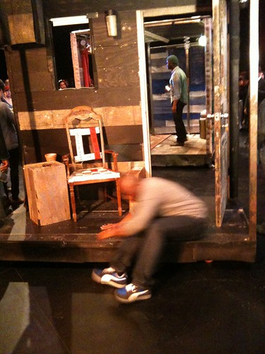 Marc Bamuthi Joseph, dancing in foreground, Theaster Gates through the open door