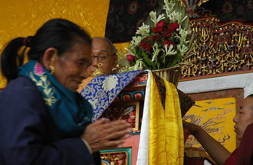 Monk attending HH Dagchen Rinpoche overseeing the long life initation from his throne, pleased Tibetan woman with her hands the prayer mudra happy with the blessing, two monks, Sakya Lamdre, Tharlam Monastery stage, Boudha, Kathmandu, Nepal by Wonderlane