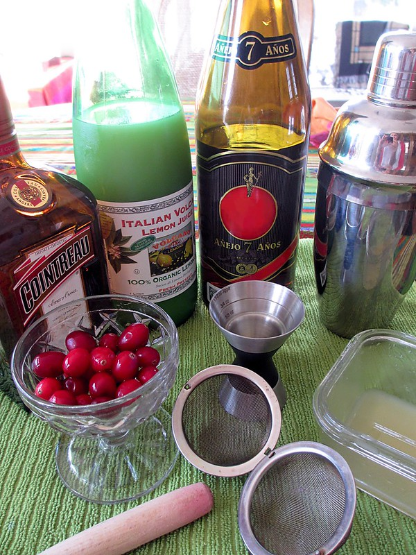 Cocktail ingredients: fresh cranberries, Cointreau, lemon juice, aged rum, and ginger syrup.