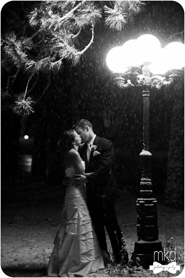 Kissing in the snow under an old fashioned street lamp