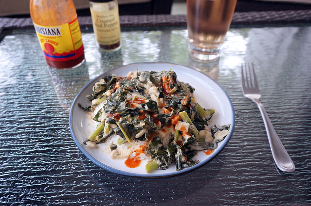 A plate of collards with coconut and peanut butter on a glass patio table, begging to be eaten. Bottles of hot sauce and crushed red pepper flakes wait toward the back of the table, as does a glass of light red-brown fizzy water with bitters
