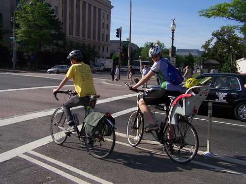 Bicyclist with a child in a rear seat carrier, Pennsylvania Avenue NW cycletrack
