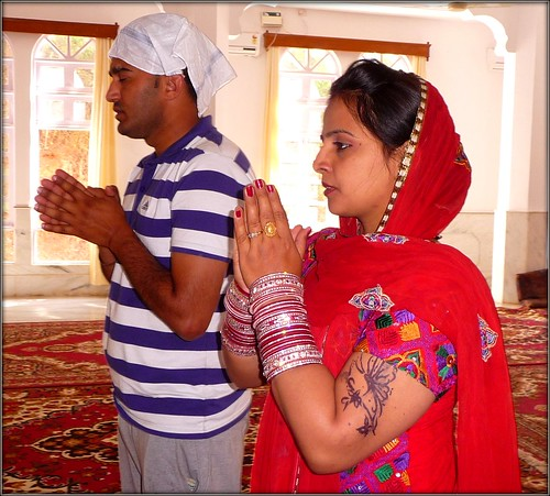 Sikh couple praying in the Gurdwara by Ginas Pics