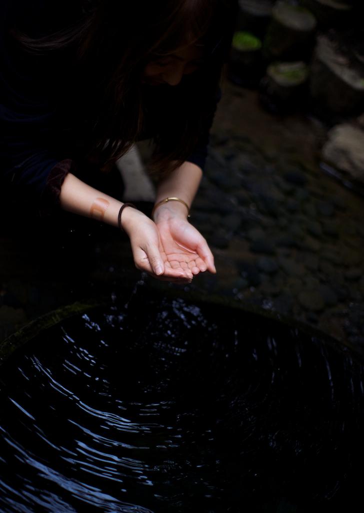 Hands purification in Kiyomasa-Ido well,  Meiji-jingu garden, Tokyo, Japan