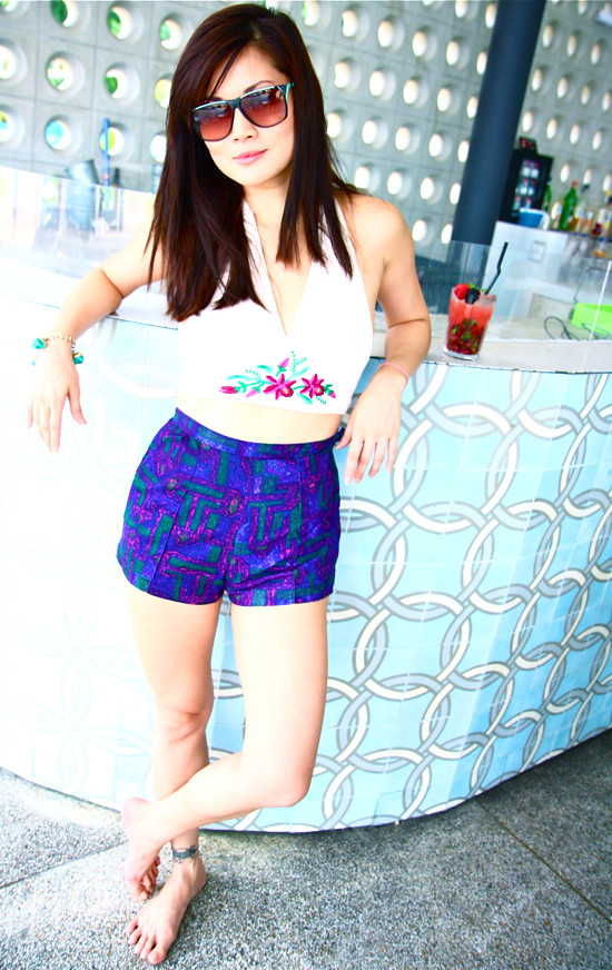 Chillin' by the bar in an embroidered 1970s halter top (S/M) worn with really cute high waist purple printed shorts (XS). A green beaded bracelet adds a jingly touch, and vintage sunglasses top it all off.