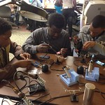 Jeremiah teaching his friends Malaino and Malik how to solder