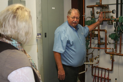 Seed company President Glen Davis explains to Business & Cooperative Program Director Dana Kleinsasser how the USDA-funded boiler heats the facility, saving 60 percent of the cost of energy.