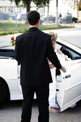 driving(0.0), bodyguard(0.0), automobile(1.0), automotive exterior(1.0), groom(1.0), wheel(1.0), vehicle(1.0), man(1.0), formal wear(1.0), luxury vehicle(1.0), ceremony(1.0),