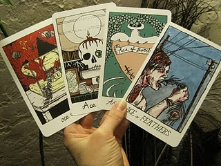 A picture of a hand holding four cards from the Collective Tarot deck