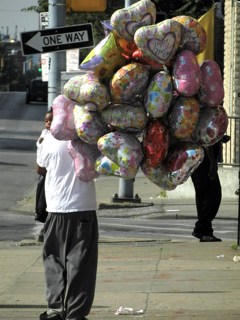 Man Carrying a Child and Helium Filled Balloons on Mother's Day 2012
