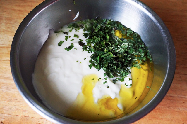 Sauce ingredients, unmixed: ivory yogurt in a stainless steel bowl, with a curl of deep yellow olive oil on one edge running into a small heap of deep green minced herbs