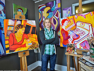 Christi Furnas, a white woman, standing among a group of colorful paintings