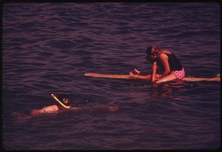 Snorkler and surfer in the waters off busy Doheny State Beach, September 1974