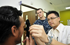 NORTH SULAWESI, Indonesia (June 6, 2012) Hospital Corpsman 2nd Class Alan Kampert watches a local Indonesian doctor check the eye sight of a patient during Pacific Partnership. (Photo by Kristopher Radder)