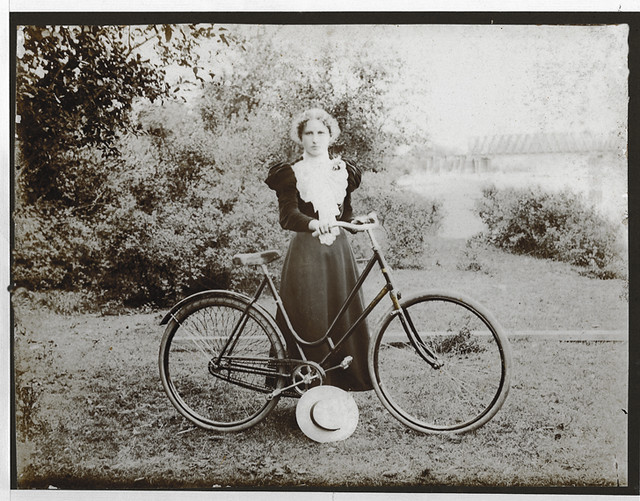 Gertrude Cone, aged about 17, in a Victorian riding outfit, standing with her ladies' bicycle at the riverside in Portland, Oregon, about 1895