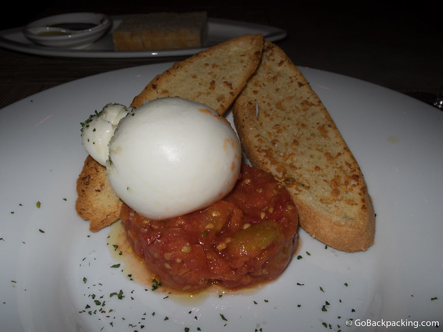 The Burrata is composed of fresh mozzarella presented on a bed of tomatoes, with crusty bread and a touch of sea salt
