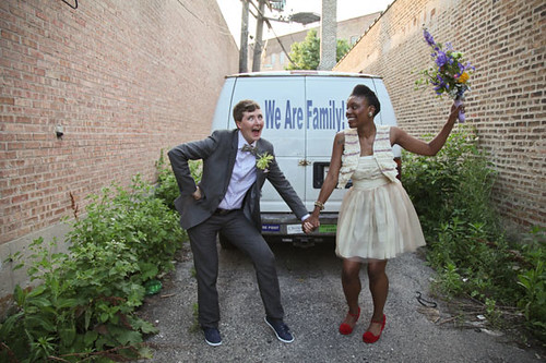 a queer couple dancing in front of a van that says we are family on the back